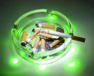 Aschenbescher mit letzter Zigarette, Qualm und Kippen